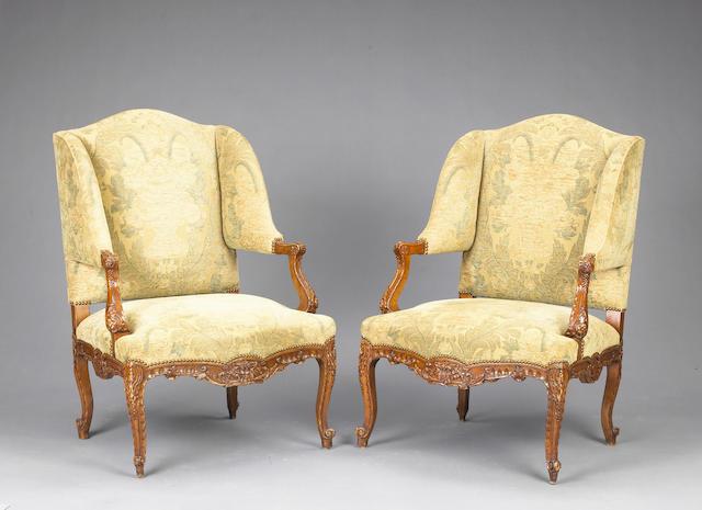A pair of Louis XV style walnut fauteuil aux oreilles