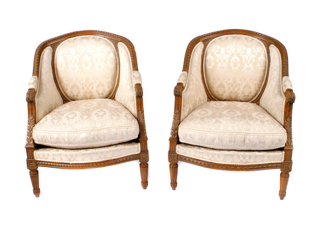 A pair of Louis XVI style walnut bergeres