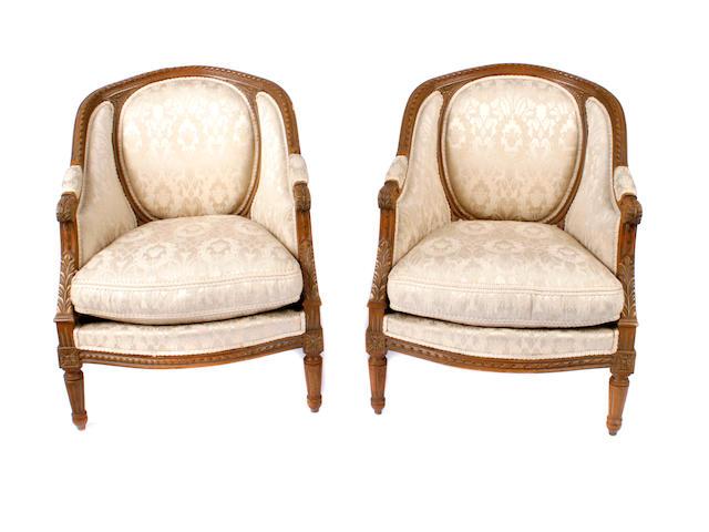 A pair of Louis XVI style walnut bergeres