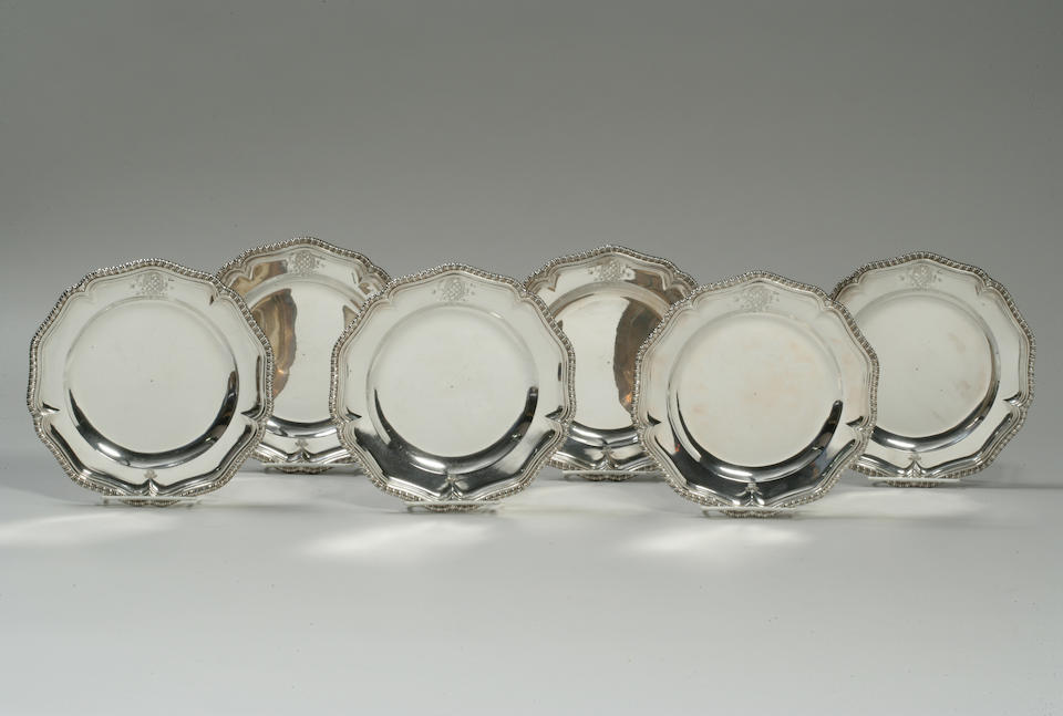 "A Set of twelve George II silver dinner plates Paul Crespin, London, 1744 Each shaped border engraved with baronial coronet opposed by an armorial emblem, with a gadrooned rim, each underside engraved ""No 1"" through No 12"" and with scratch weights, approx. 218 ozs. troy Length: 9 1/2in. (24.1cm)"