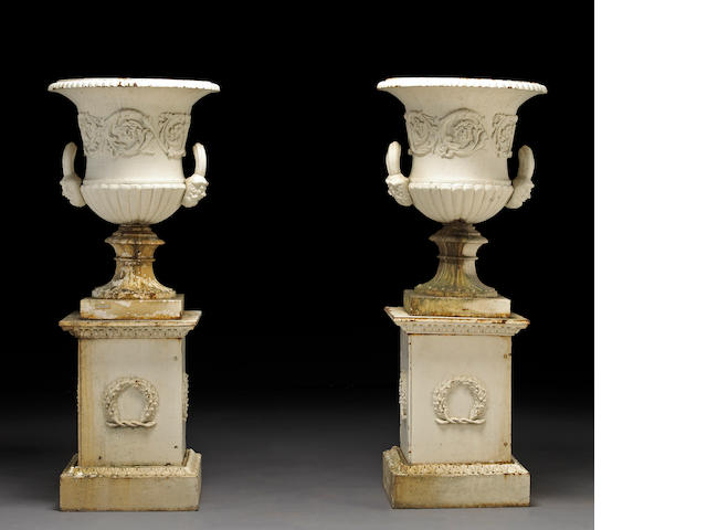 A pair of French Neoclassical white painted cast iron urns on pedestals
