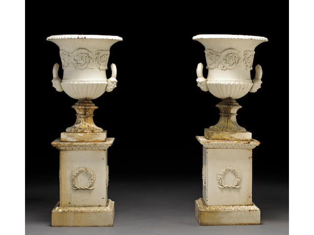 A pair of French Neoclassical style white painted cast iron urns on pedestals