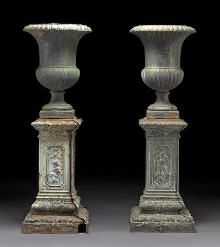 A pair of painted cast iron campana form urns on pedestals