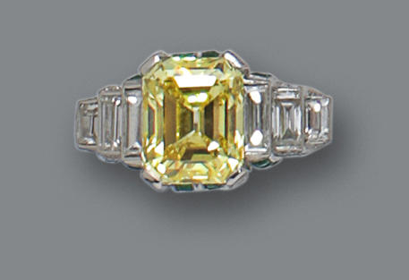 A fancy colored diamond, diamond and emerald ring