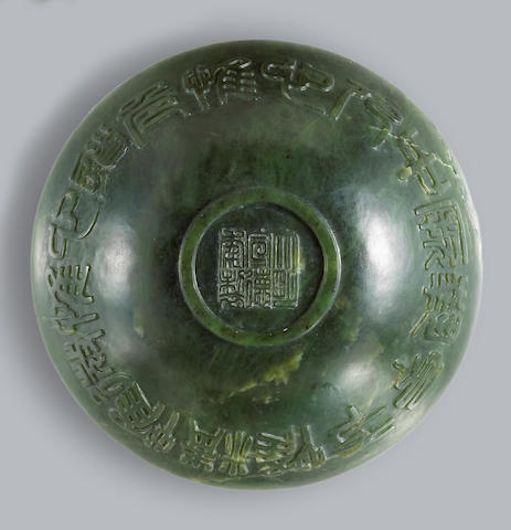 A Chinese 'spinach green' jade bowl, carved with characters (repaired chip)