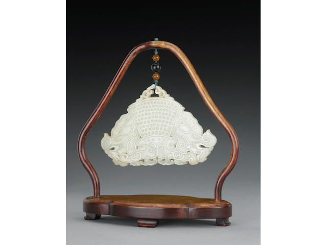 A Chinese off-white nephrite reticulated plaque of chime form with wood stand