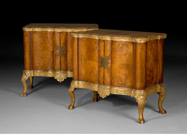A pair of German Baroque style parcel gilt side cabinets