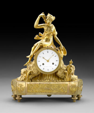 An Empire gilt bronze mantel clock surmounted by Dianna