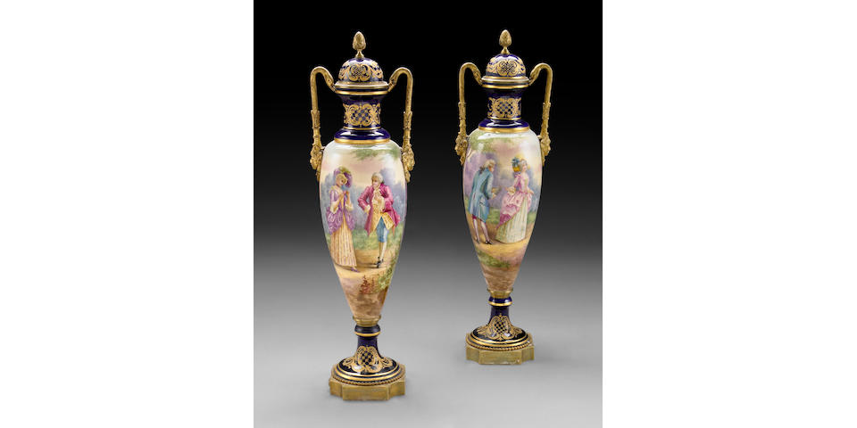 A pair of gilt bronze mounted Sevres style earthenware urns