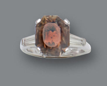 A fancy dark orangy-brown diamond and diamond solitaire ring