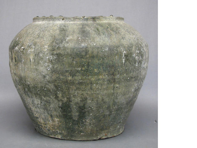 A Chinese reddish buff earthenware jar with iridescent olive green glaze, Han Dynasty