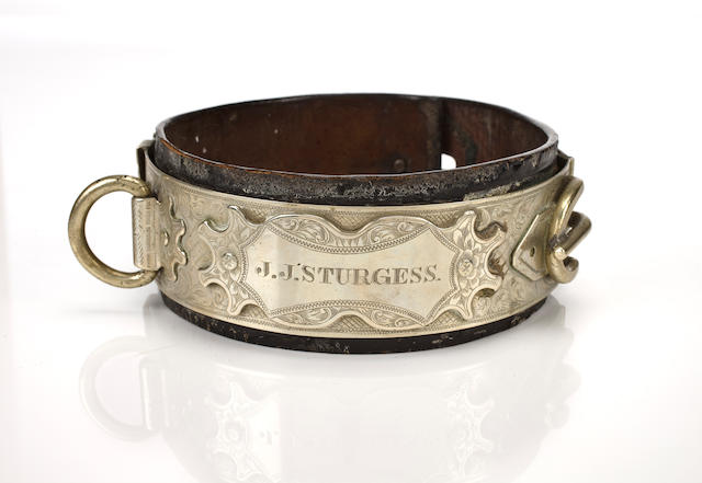 An engraved, silvered metal and leather collar, British, 19th century  in the Baroque taste with lead ring and padlock, inscribed 'J.J. Sturgess; height 2 1/2 in. (6.3 cm.)