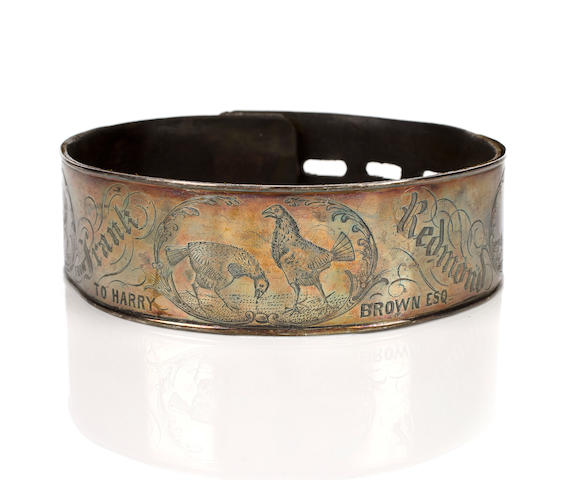 An engraved silvered metal and leather collar, British, 19th century with working padlock and key, decorated with depictions of bull and bear baiting and cockfighting, inscribed 'From Frank Redmond to Harry Brown Esq_' and further inscribed 'To Captain W.H. Patten Saunders K.C.G.', diameter 5 3/4 in. (14.6 cm.)