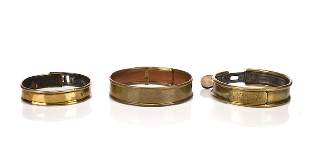 A group of three brass collars British, 19th century of medium size, each with leather liners and padlocks, one inscribed 'W. Smith/Rushenden' largest diameter 4 1/2 in. (11.4 cm.)
