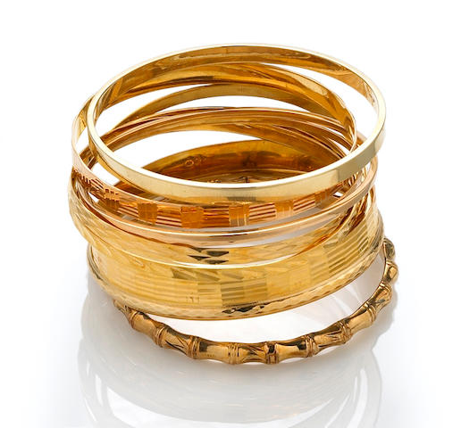 A collection of eleven eighteen and fourteen karat gold bangles
