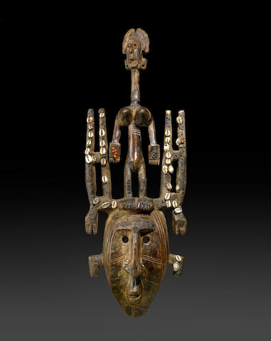A Bamana Segou style mask, the face surmounted by a standing figure