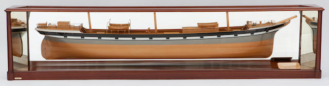 "A shipbuilders' half block model of the sailing ship ""East-Indian"" for Lang & Fulton of Greenock Scottish, circa 1894. the hull built-up with laminated wood in 1/8 in.:1 ft. scale, and painted with grey, white and black topsides with gun ports, the deck detailed with lifeboat on davits, gilt brass fittings throughout, deckhouse, (3) truncated masts, handrails ship's wheel and binnacle, navigation lamps and capstan. Displayed with a wood plaque lettered ""Ship/""East-Indian""/Reg. Dim. 252.4. 39.05.22.5 Gross 1745.66/built by/Robert Duncan & Co. Ltd./ Port-Glasgow/1894"", in a glazed mahogany case with mirror back and ends. 56 in.(142.2 cm.) length"