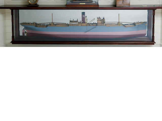 "A shipbuilders' mirrored back half model of the S.S. ""North Cornwall"" for the North Shipping Co. Scottish, circa 1924. the hull built up in lifts in 1/4 in.=1 ft. scale, painted with a red bottom, wide salmon colored waterline and grey topsides with the name applied to the bow, and a lowered gangway. The decks are of maple veneer with the plating and other details drawn in India ink. The decks are detailed with anchor windlass, ventilators, bollards, deck railings, deck hatches, stump masts with cargo booms, double bridge with enclosed bridge wings, ladders, stanchions, life boats on davits, running lights, funnel, brass propeller and rudder and numerous other details. Mounted on a front-silvered mirror within a mahogany framed case with turned corner columns. 109 in.(175.2 cm.) cased length."