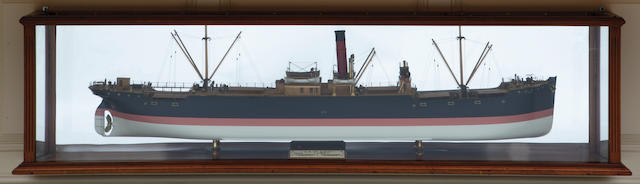 "A shipbuilders' half block model of the freighter S.S. ""St Eric"" the hull built up from the solid in lifts in 1/4 in.=1 ft. scale model with a white painted bottom, broad salmon pink waterline and black topsides, the deck fitted with nickel-silver and brass fittings including helm and binnacle, ventilators, (2) life boats on davits, bridge with engine telegraphs and Kelvin-type binnacle. With an ivorine plaque lettered: S.S. St. Eric Builders John Blumer & Co Sunderland, Owner A D Wilson Esq Gothenburg. Displayed within a glazed mahogany case with back mirror. 74-½ in.(189.2 cm.) cased length."