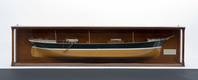 A shipbuilders' half model of an iron merchant clipper ship Scottish, circa 1870. the hull built up in lifts in 1/4 in.=1 ft. scale, unpainted below the waterline and with black topsides above, carved figurehead, three truncated masts, deck details include hand rails, deckhouse, winches, lifeboat on davits, lowered gangway, helm and binnacle, and other details. Displayed in a mahogany case with solid back, turned corner pillars and inscribed ivorine plaque. 80 in.(203.2 cm.) cased length.