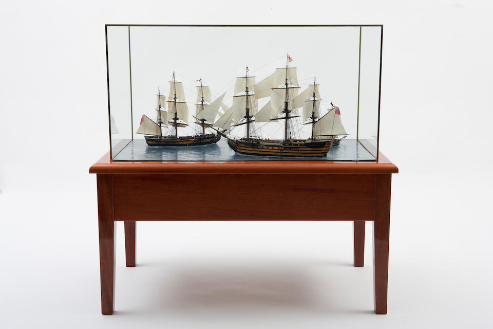"""A diorama entitled """"Rendezvous with Nelson"""" By Arthur Clark (Hitchcock family, 20th century) A clear-water diorama depicting a well detailed model of Lord Nelson's flagship under full sail meeting the 36-gun frigate H.M.S. Euralyus and the British cutter Dart. Each model, is set into the glass sea and detailed with built up and painted hulls, planked decks, numerous deck details including figure heads, pin and fife rails, ship's boats, cannons rigged on carriages, masts with standing and running rigging, sails with seam panels (some furled), figures on deck, and other details."""