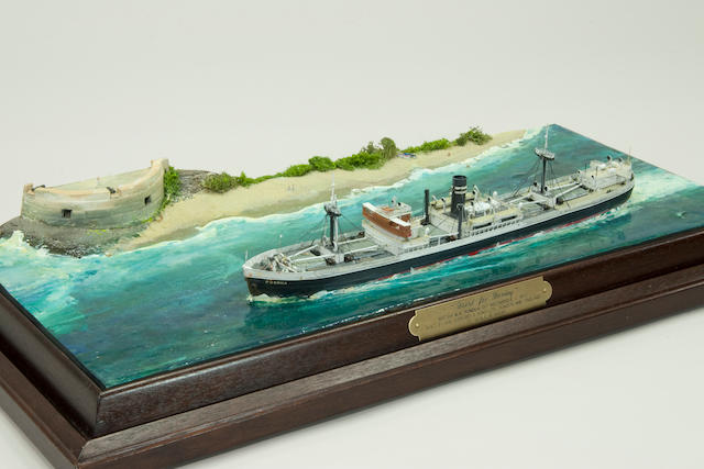 "A diorama ""Bound for Bombay"" of the British steamer ""Punda"". by Robert H Mouat (British, 20th century) the model, in 1/6 in.=1 ft. scale, of the steamer passing a fortification off Mozambique, set in a modeled and painted sea, the hull weathered and well detailed with deck houses, port holes, boats on davits, ladders, railings, and other details. Displayed in a brass framed glass case with a mahogany base. 22-½ x 8 x 11 in.(57 x 20 x 28cm.) cased."