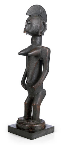 A Bamana female figure with hands resting on the abdomen  height 22 1/2in