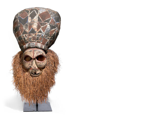 A Suku mask with fiber headcrest and raffia beard height 34in