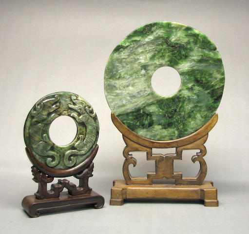 Two jade disc bi, one plain, one carved with dragon, stands