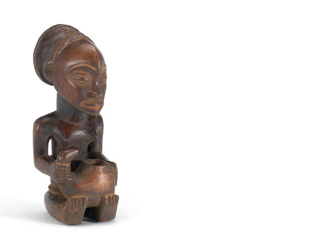 An African carved wood figure of a seated woman