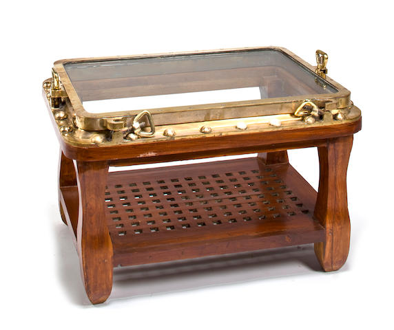 A glass, brass and mahogany nautical coffee table  Modern, 21st century 35 x 25 x 22 in. (88.9 x 63.5 x 55.9 cm.)