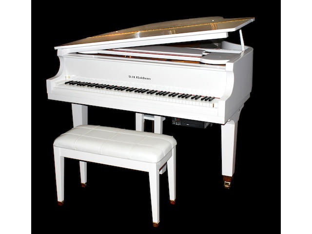 A D.H. Baldwin white lacquered grand piano and bench with an electronic disc player