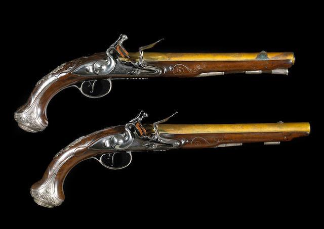 A pair of silver-mounted English flintlock pistols by John Bumford