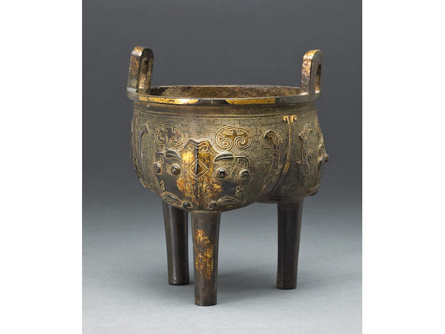 A partially gilt bronze tripod censer