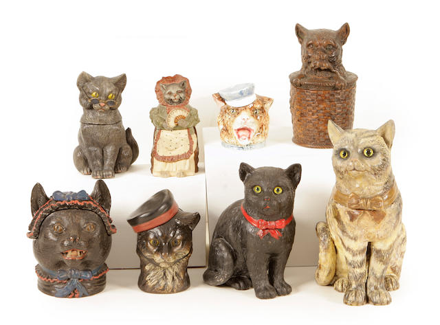 A group of eight Continental earthenware and porcelain tobacco jars of feline interest