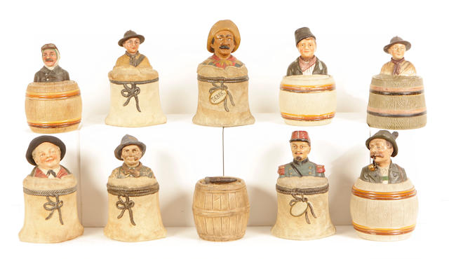 A group of ten earthenware tobacco jars in the form of barrels and sacks with figural lids