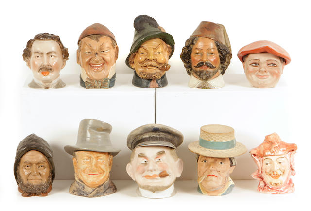 A group of ten Continental earthenware tobacco jars modeled as heads