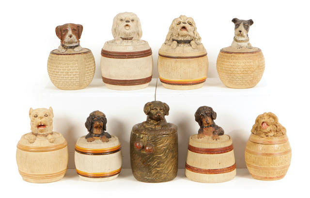 A group of nine Continental earthenware tobacco jars modeled as barrels with hound finials