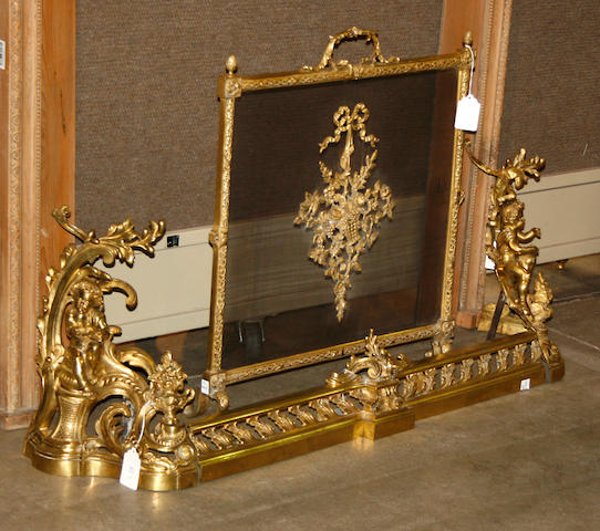 A pair of Louis XV style gilt bronze figural chenets and fire front, and Louis XVI style gilt bronze and mesh firescreen late 19th/first half 20th century