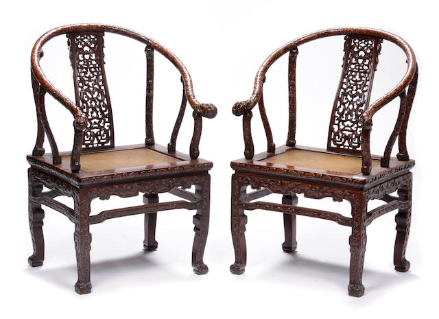 A pair of Chinese carved hardwood horseshoe bacck armchairs