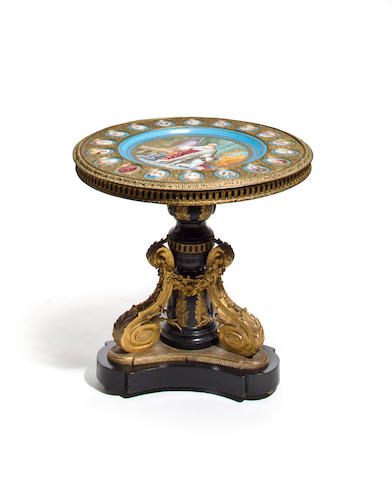 A Napoleon III gilt bronze mounted ebonized center table with a Sevres style porcelain top second half 19th century