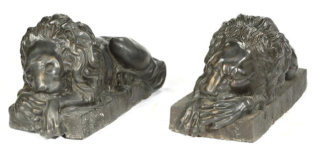 A pair of patinated bronze models of recumbent lions<br>late 20th century