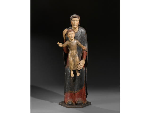 A Spanish Romanesque style carved wood and polychrome decorated figure of the Virgin and Child <br>probably 13th century, restored