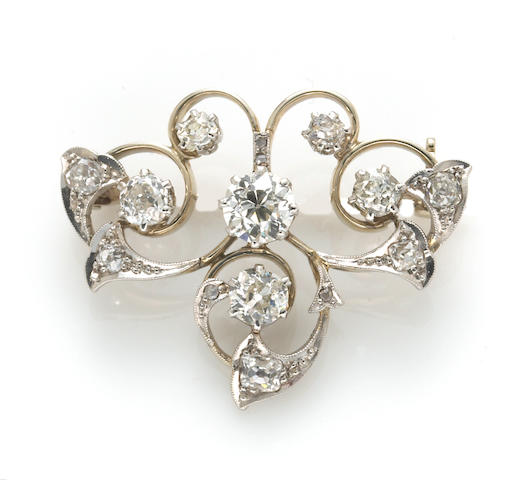 An antique diamond scroll brooch,