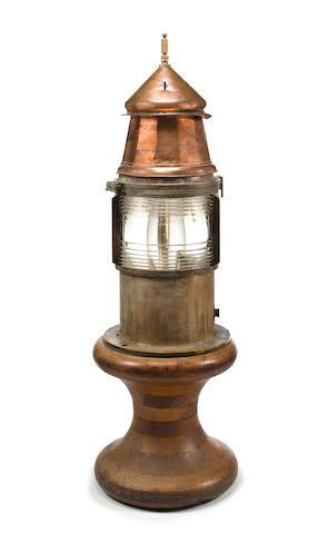 A buoy lantern with a fresnel lens 56-1/2 x 19 in. (143.5 x 48.2 cm.) height x diameter.