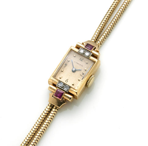 A retro diamond, ruby and fourteen karat gold integral bracelet wristwatch, Tiffany & Co.,