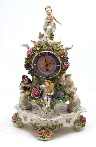 A German Sitzendorf porcelain floral and figural encrusted mantle clock on separate base