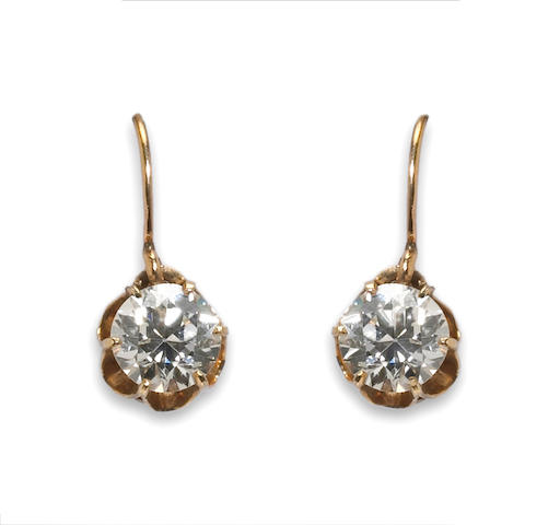A pair of diamond solitaire earrings