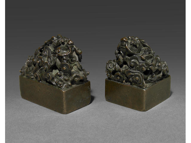 A pair of Chinese bronze seals with dragon terminals