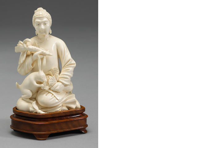 A Chinese carved ivory figure of a seated woman with carrot, on base 20th century